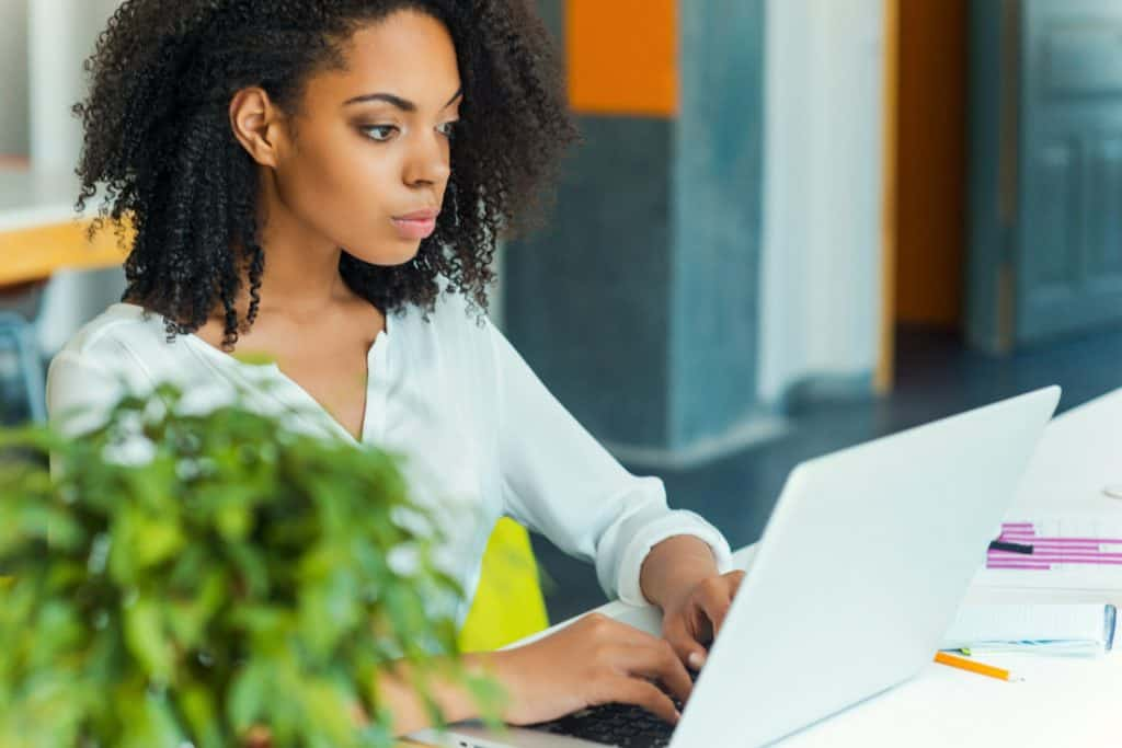 Woman on laptop with plant on desk