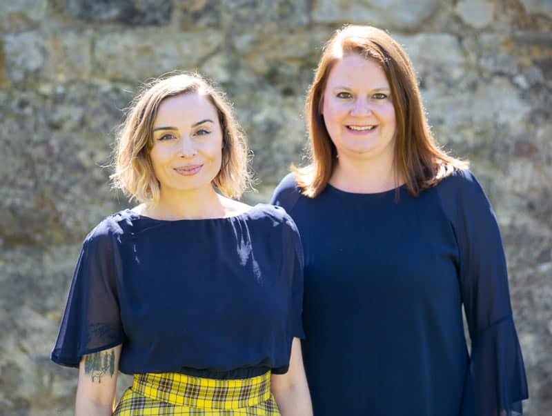Gemma and Laura from Make Traffic Happen standing against a wall smiling to camera